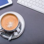 Kaffeetasse umrahmt von Tastatur, Smartphone und Tablet